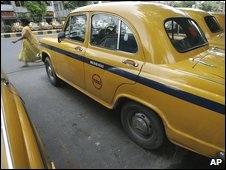 A woman walks passed a line of yellow taxis in Calcutta, 24 July 2009
