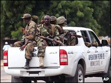 Armed soldiers on patrol in the back of a white pick-up truck in Maiduguri on 1 August
