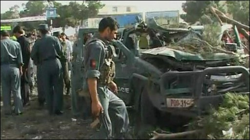 A man inspects the wreck of a car following a blast in Herat