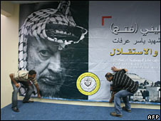 Palestinians install a poster bearing a portrait of late Palestinian leader Yasser Arafat in Bethlehem