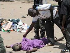 Nigerian police officers inspect body of dead militant
