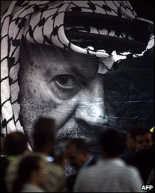 Fatah members stand near a portrait of late Palestinian leader Yasser Arafat