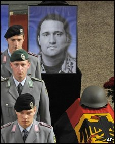 Soldiers stand in front of photographs of German soldiers killed in Afghanistan during a commemoration service in Bad Salzungen, Germany, 2 July 2009