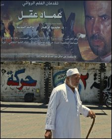 """A Palestinian man walks past a billboard advertising the film """"Emad Akel"""", the first motion picture production of the Islamic group Hamas"""