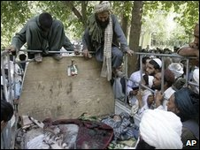 Afghan villagers look at the bodies of the two children and a villager