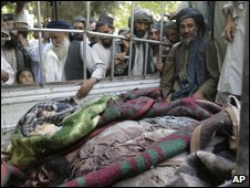 Afghan villagers look at the bodies of several people allegedly killed in an airstrike in Kandahar, on 5 August 2009