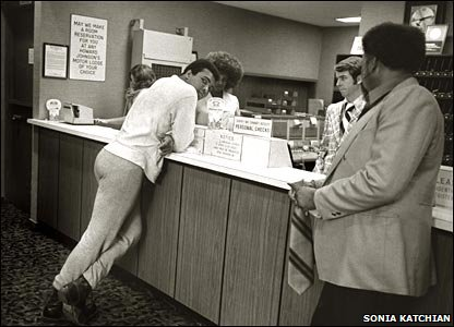 Muhammad Ali toys with a rather serious-looking hotel desk clerk in Detroit in 1974. Copyright Sonia Katchian.