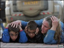 An Israeli woman and her children take cover from rocket attacks in Kfar Aza (7 January 2009)