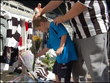 Young boy laying tribute to Sir Bobby Robson