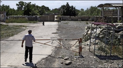 A man stands near the closed boundary barrier between the Georgian village of Ergneti and Tskhinvali, regional capital of Georgia's breakaway province of South Ossetia, 5 August 2009