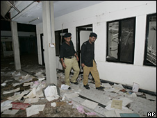 Pakistani police officers visit offices of a factory ransacked by angry labourers in Sheikhupura near Lahore