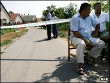 Local citizens sit on chairs as Hungarian policemen secure an area in Kisleta, Hungary, 3 August 2009