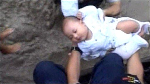 A baby is rescued from floods in the Philippines