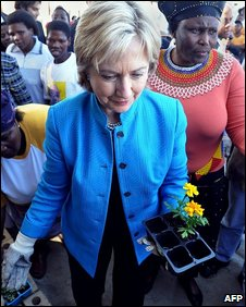 Hillary Clinton carries a flower at a housing project near Cape Town, South Africa, 8 August 2009