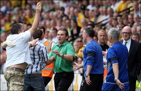 A Norwich fan throws his season ticket at manager Bryan Gunn