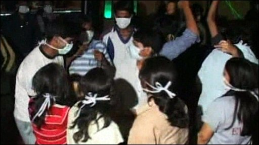 Party-goers in India wear Swine Flu masks
