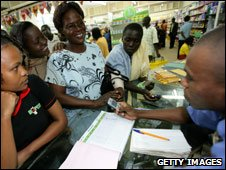Customers in a Kenya supermarket using mobile phones to transfer and withdraw money