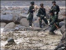Soldiers struggle to make their way across rapids to trapped residents from the flooded village of Hsiaolin in Taiwan on Tuesday (image released by Taiwan Military News Agency)