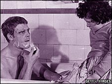 Father shaving in bath as daughter sits close by