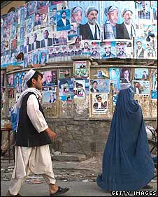 People walk past wall covered with election posters in Kabul