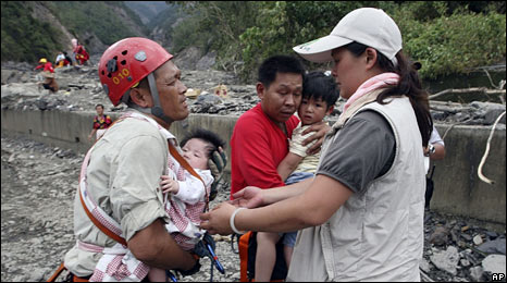 Taiwanese rescuers hold babies before crossing the river to evacuate the flooded village of Liugui in Kaohsiung county