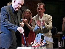 Sir Alan Ayckbourn cuts his cake.
