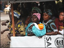 Displaced people watch as Hillary Clinton tours their camp near Goma, DR Congo, 11 August 2009