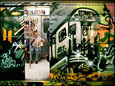 A man reading on a New York subway train decorated with graffiti (Picture: Martha Cooper, Subway Art, Chronicle Books 2009).