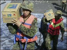 Soldiers carry supplies for typhoon victims