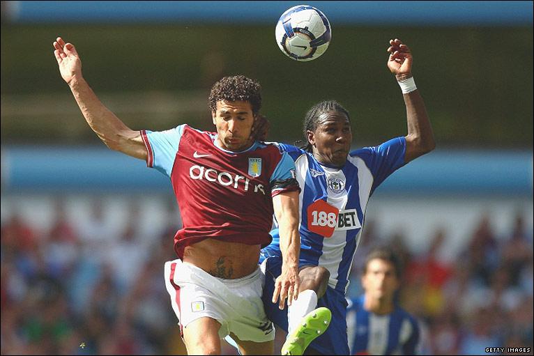 Hugo Rodallega of Wigan challenges Villa's Carlos Cuellar for the ball