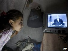 An Afghan girl listens to President Hamid Karzai on TV during the live debate in Kabul on 16 August 2009