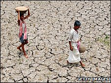 Two children walking across parched soil (Getty Images)