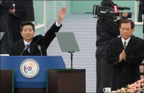 Former South Korean President Roh Moo-Hyun (L) waving, while outgoing President Kim Dae-jung (R) applauds, 2003
