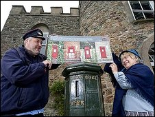 image shows the two people holding an image of the stamps above the oldest postbox