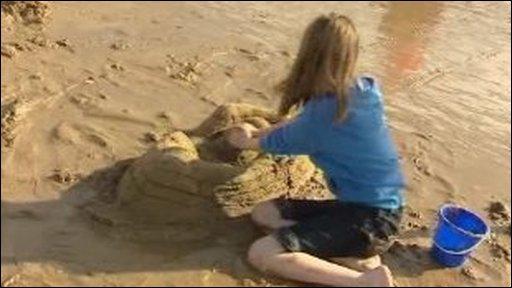 Girl builds sandcastle