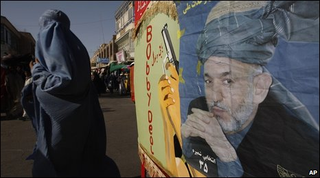 A woman walks past a poster of Afghan President Hamid Karzai (18 August 2009)