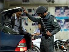 Afghan policeman checks inside of a car in Kabul (19 August 2009)