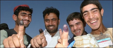 Men show off their inked fingers after voting in Lashkar Gah, Helmand, on 20 August 2009