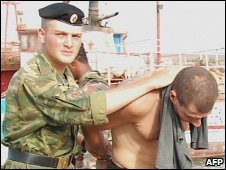 A Russian military official escorts one of the eight suspected hijackers at the Cape Verde island of Sal, 19 August 2009