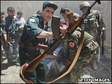 Afghan police drag the bodies of two gunmen killed in a gunfight in Kabul on 20 August 2009