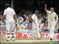 Australian bowler Peter Siddle (R) celebrates the wicket of England's Alastair Cook (L)