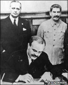 Soviet Foreign Minister Vyacheslav Molotov signs the Nazi-Soviet pact as his German counterpart Joachim Von Ribbentrop (left), and Stalin look on, Moscow, 23 August 1939
