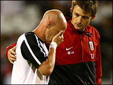 Andy Johnson is consoled by the Fulham physio as he leaves the pitch