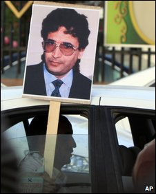 A Libyan driver holds a placard of Lockerbie bomber Abdelbaset Ali al-Megrahi, 20 August