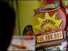 A man checks his SuperEnalotto tickets in front of a billboard showing the jackpot 146.9m jackpot in Rome, 22 August 2009