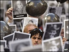 Bereaved hold pictures of the dead