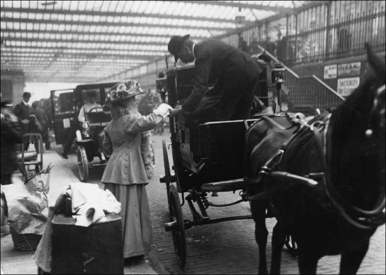 A woman pays a cab driver at Paddington Station