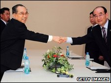 Kim Young-Chol (R), chief delegate and secretary general of the South Korean Red Cross office and Choi Sung-Ik of North Korea shake hands , 26 August