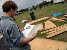 Man looking at plans by wood