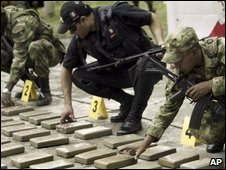 Colombian police and soldiers examine seized packages of cocaine